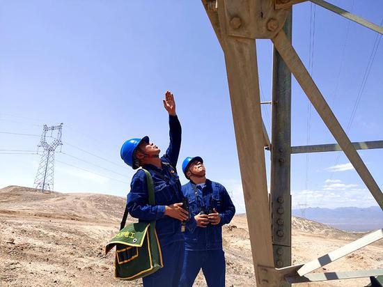 7月6日,新疆吐鲁番供电公司输电运检工韩光亮与徒弟开沙尔·买合苏提冒着47摄氏度高温,在火焰山对220千伏吐番南一线开展高温特巡。折伟亚 摄