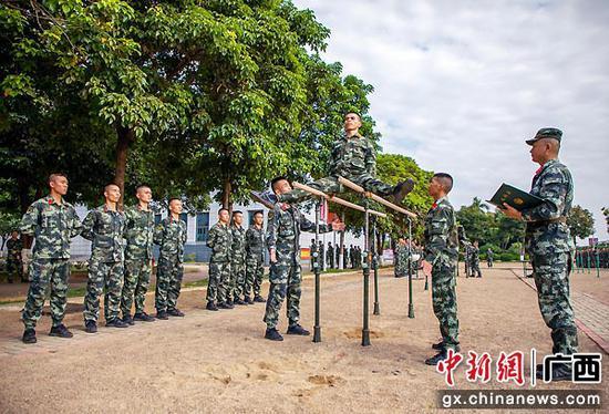 7月8日,集訓官兵正在進行器械屈身分腿坐杠課目考核。