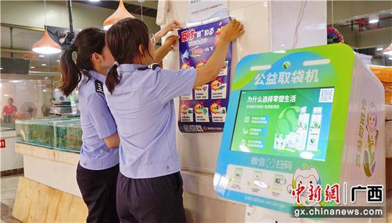 民警在菜市粘貼反詐海報。警方供圖