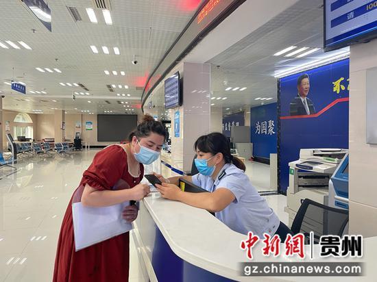 """导税台工作人员指导纳税人使用""""无声叫号""""服务 陈露丹 摄"""