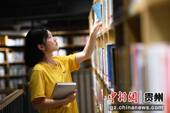 7月21日,一名读者正在贵阳市南明区图书馆内挑选自己喜爱的书籍。