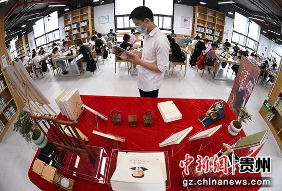 7月21日,一名读者正在贵阳市南明区图书馆红色经典阅读区阅读书籍。