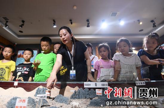 7月20日,在贵州陨石文化科普馆,工作人员正通过罗布泊陨石散落带沙盘向小朋友们介绍陨石散落分布。