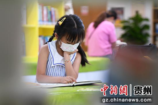 7月21日,一名小读者正在贵阳市南明区图书馆内阅读儿童图书。