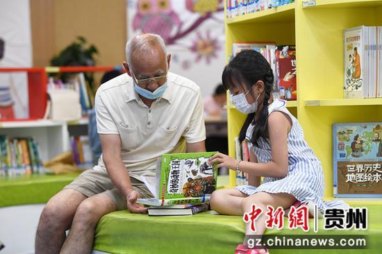 7月21日,在贵阳市南明区图书馆内,一名小读者正在家人的陪同下阅读儿童图书。