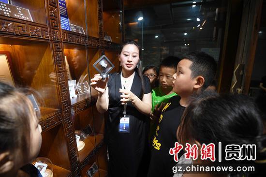 """7月20日,贵州陨石文化科普馆的工作人员正在向前来参观的小朋友们展示被称为""""天外来客""""的陨石。"""