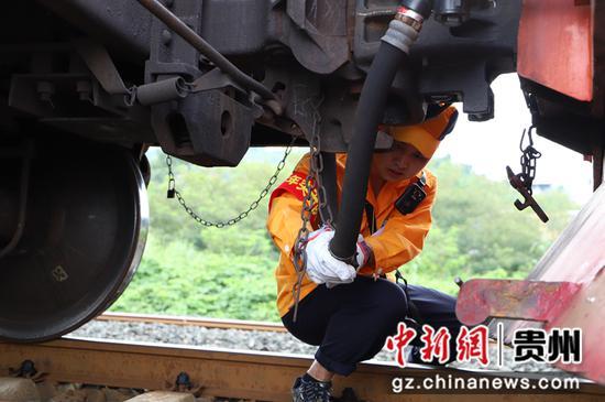 图为调车长正在进行摘接风管作业。