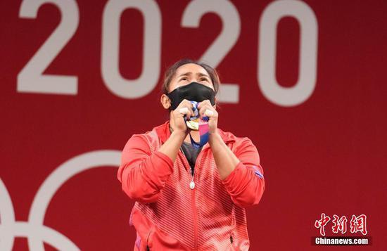 7月26日,菲律賓選手迪亞茲手捧金牌。當日,東京奧運會舉重女子55公斤級比賽在東京國際論壇大廈舉行。菲律賓選手迪亞茲獲得冠軍。這也是菲律賓獲得有史以來第一塊奧運金牌。 中新社記者 杜洋 攝