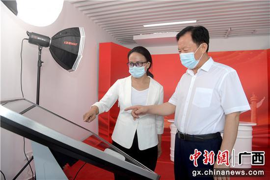 圖為廣西壯族自治區黨委常委、統戰部部長徐紹川(右)觀看中新社廣西分社新媒體產品。俞靖 攝