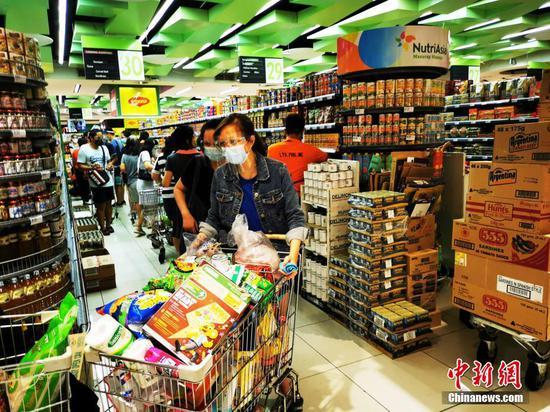 """當地時間7月31日,菲律賓首都馬尼拉CBD馬卡蒂一生活超市,市民采購副食品,備戰即將開始的第三度封城。該市將在8月6日至8月20日再度實行""""加強社區隔離"""",政府安排7月30日至8月5日為緩沖期,供各方提前準備。中新社記者 關向東 攝"""