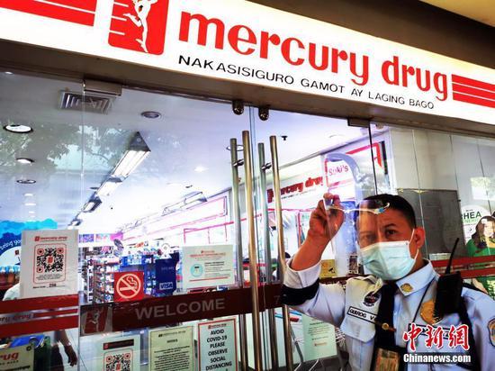 """當地時間8月6日,由于菲律賓感染德爾塔毒株病例呈上升趨勢,首都大馬尼拉地區第三度實行""""加強社區隔離"""",并將延續到20日。圖為馬尼拉CBD馬卡蒂綠帶商圈一藥店仍營業,但保安限制進入店堂人數。 中新社記者 關向東 攝"""