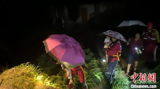 圖為消防員在泥濘小路上轉移被困孩童?!〗楆柨h消防救援大隊供圖