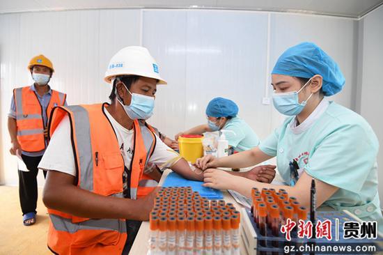 8月12日,貴州退休醫師醫院的醫護人員正在為中建二局的建筑工人進行抽血檢查。