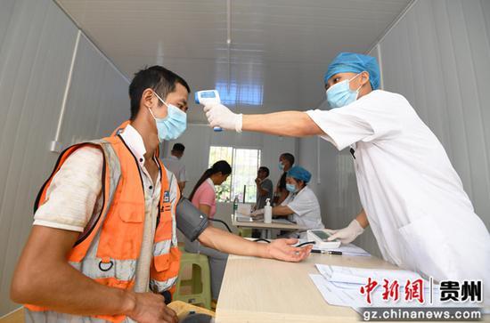 8月12日,貴州退休醫師醫院的醫護人員正在為中建二局的建筑工人測量體溫和血壓。