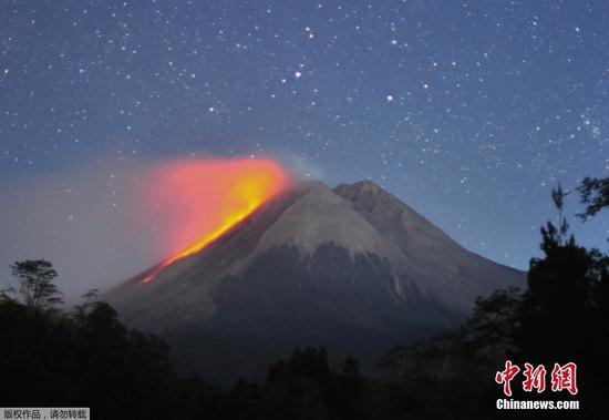 當地時間8月11日,印度尼西亞日惹市的斯勒曼,熾熱的熔巖從默拉皮火山噴涌而下,與星空相輝映。