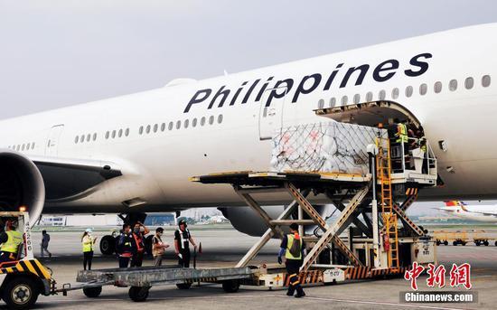 当地时间8月20日,中国政府援助菲律宾的新一批新冠疫苗由菲律宾航空公司运抵马尼拉。图为菲律宾工作人员在马尼拉国际机场卸下疫苗。 中新社记者  关向东 摄