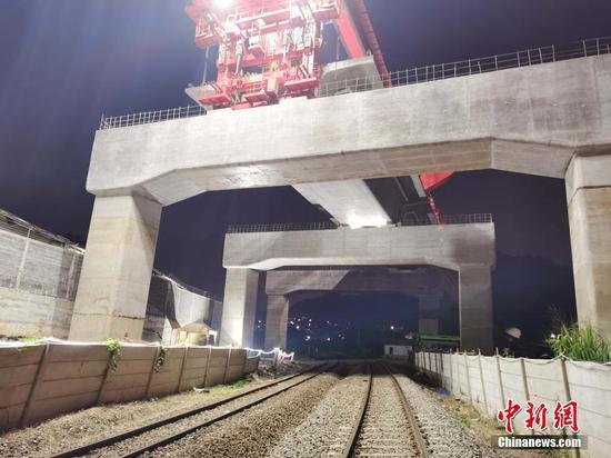 8月22日,印尼雅万高铁4号梁场万隆往雅加达方向DK1114桥上,高铁全线唯一一处上跨印尼既有铁路箱梁架设完成,标志着项目建设又一重大高风险工程施工取得突破。图为8月21日的架设施工现场。 中新社发 王增堃 摄