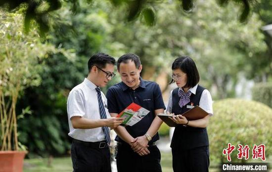 """银行工作人员向某企业负责人介绍""""贷款码""""。 人民银行杭州中心支行供图"""