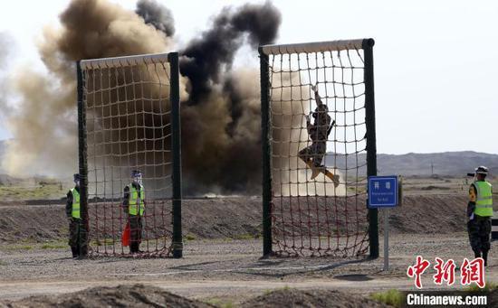 乌兹别克斯坦参赛队员翻越网墙。 王小军 摄
