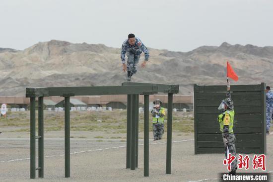 综合赛上,中国海军参赛队主射手易明正在通过断桥。 王浩 摄