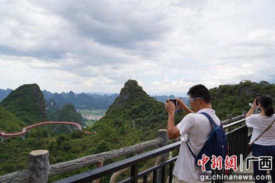 图为游客在桂林阳朔如意峰景区观赏喀斯特峰林地貌。王猛  摄