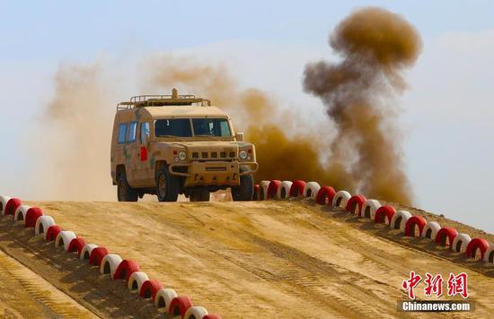 中国参赛队员驾驶车辆翻越陡坡。 王小军 摄