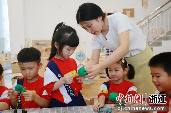 非遗传承人沈敏儿在教小朋友们制作民间布艺作品  俞大庆 摄