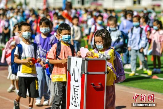 图为一年级新生将自己制作的心愿卡投入心愿箱。 中新社记者 刘新 摄