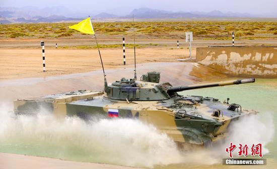 """8月30日,""""国际军事比赛-2021""""中国库尔勒赛区,""""苏沃洛夫突击""""项目最后一轮单车赛在雨中拉开战幕,中国、俄罗斯、白俄罗斯、委内瑞拉四国参赛队展开激烈角逐。中国""""猛虎""""车组以15分31秒43的成绩取得当日比赛第一名,俄罗斯、白俄罗斯分别位列第二、三名。至此,""""苏沃洛夫突击""""项目单车赛3轮12个车组的比赛全部完成,中国队以单车赛总成绩47分25秒72排名第一,打破赛事纪录,俄罗斯队、白俄罗斯队位列第二、三名。图为俄罗斯参赛队选手驾驶步战车驶入涉水场。 中新社记者 王小军 摄"""