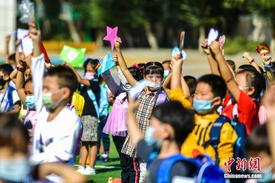 图为一年级新生展示自己制作的心愿卡。 中新社记者 刘新 摄