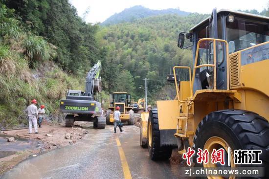 暴雨过后,大型机械进行路面清障。  田双双 摄