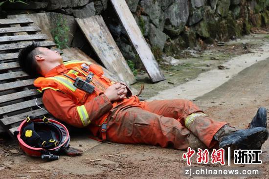 暴雨过后,消防员席地短暂休息。  田双双 摄