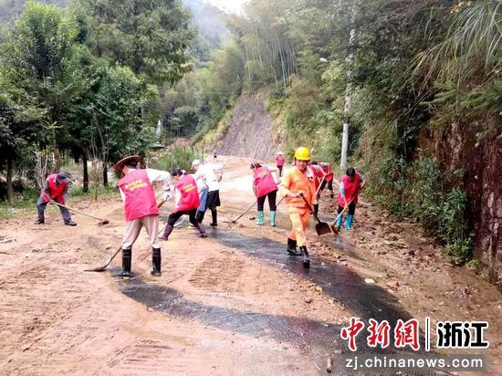 暴雨过后,工作人员进行路面清淤。  田双双 摄