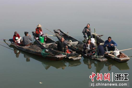 渔民们聚一起在船上吃饭  朱伟 摄