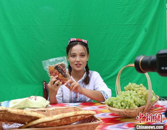 """中国农民丰收节""""社企对接助发展 农民合作社庆丰收""""专场活动在新疆吐鲁番市举办。图为主播现场宣介。 胡嘉琛 摄"""