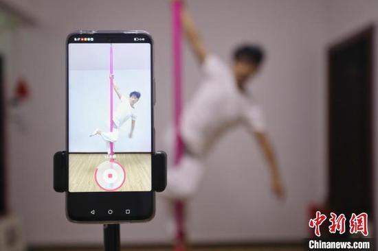 张细达用手机拍摄钢管舞练习视频。 瞿宏伦 摄