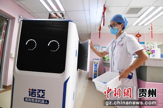 9月14日,贵阳市妇幼保健院南明分院儿科住院部医师正在从诺亚医院物流机器人上取出药品。