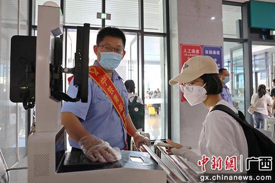 图为桂林站工作人员帮助旅客检票出站。陈雨雨 摄