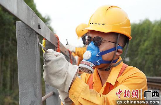 玉林工务段桥梁工顶高温整修涂装黎湛线锈蚀桥梁栏杆,保障桥梁设备安全。谭育俊  摄