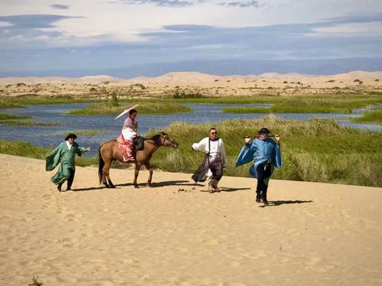"""近日,科克托海湿地吸引了不少游客来这里冲沙,一部年轻人的""""古装戏""""正在这里拍摄。(张旭茗 摄)"""