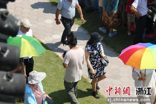 因天气炎热,一位游客将包装袋套在头上遮阳。  周孙榆 摄