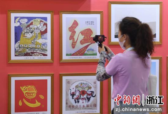 参观者拍摄红色动漫作品。  王刚 摄