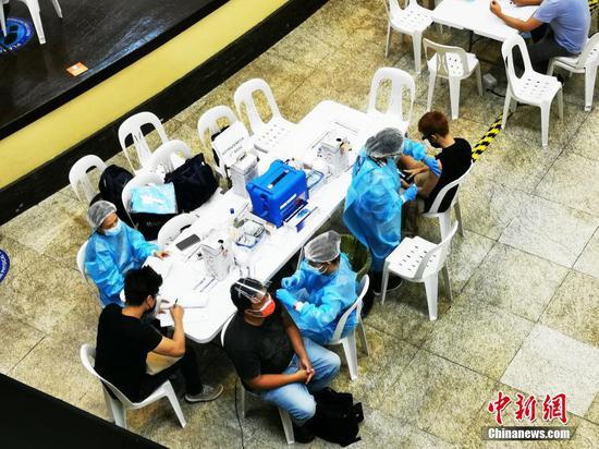 """当地时间10月4日,为鼓励人们接种疫苗,菲律宾卫生部与菲律宾娱乐和游戏公司设立""""接种疫苗赢百万比索""""活动。图为当日,设在大马尼拉CBD马卡蒂一大型商场内的接种点,市民踊跃接种疫苗。 中新社记者 关向东 摄"""