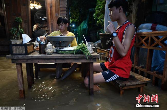 泰国暖武里府遭遇洪水餐厅被水泡 顾客水中淡定吃饭