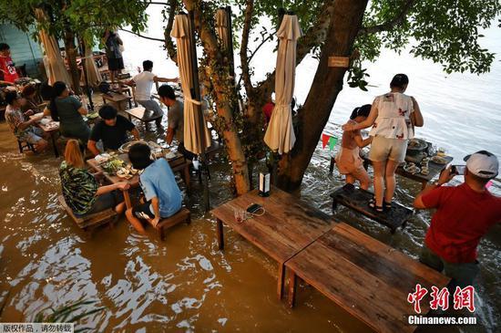 当地时间2021年10月7日,泰国曼谷北部暖武里府,当地遭遇洪水,当积水涌入河边的一家餐厅时,大部分民众依旧淡定享用晚餐。