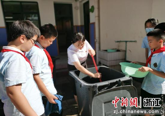金华开发区江滨小学教师俞俊带领学生学习清洗垃圾桶。   金程 摄