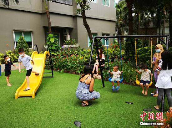 当地时间10月10日,印尼首都雅加达的一公寓小区,居民带着小孩子在游玩。截至当天,印尼已有超1亿人接种了新冠疫苗。其单日新增确诊病例数和死亡病例数均创下去年6月底以来最低纪录。 中新社记者 林永传 摄