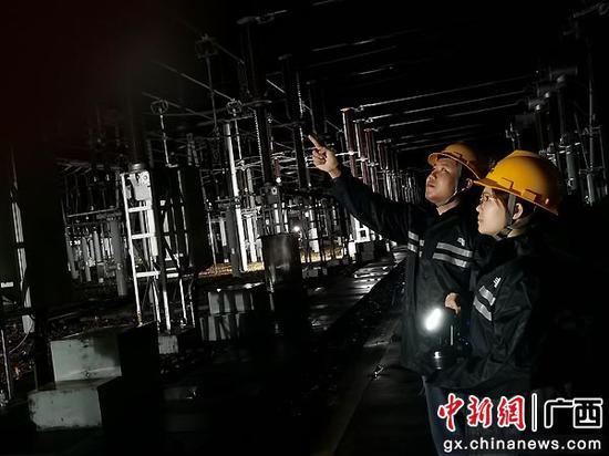 崇左供电局桃城运维班变电运维人员雨夜对高压设备开展时时监测。陈麒旭 摄