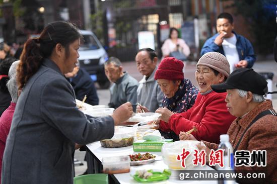 10月12日,在贵阳市南明区望城街道大正雨曦社区居委会举办的重阳节长桌宴上,老年人们正开心地共享美食。