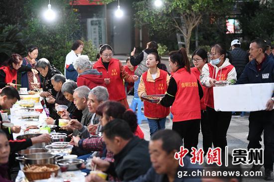 10月12日,贵阳市南明区望城街道大正雨曦社区居委会的工作人员正在重阳节长桌宴上摆放美食。